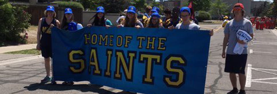 Students walking with Saints banner and high school clothing