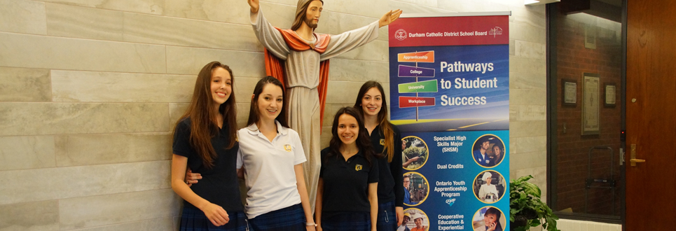 Female students standing by Pathways banner and statue of Jesus