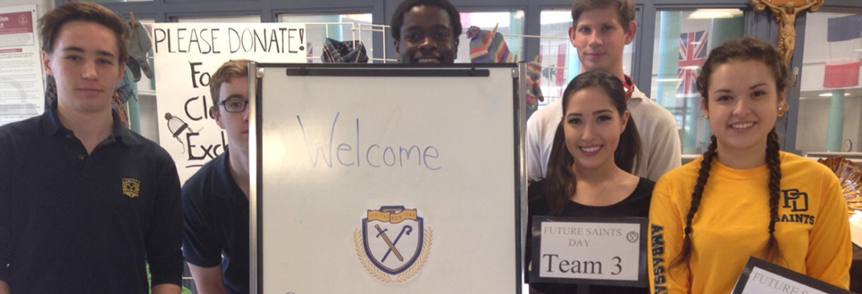 Students standing beside welcome sign